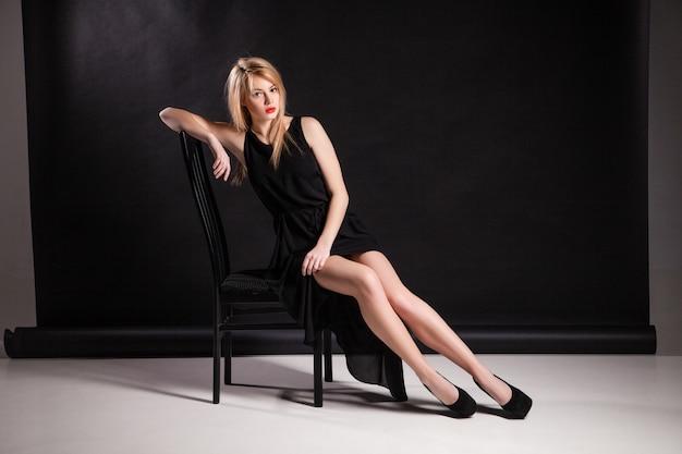 Het beeld van een mooie luxe vrouw zittend op een zwarte stoel. geïsoleerd.