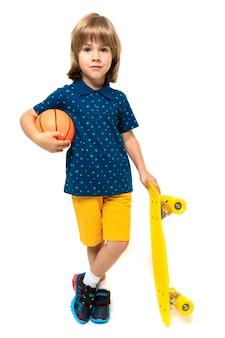 Het beeld van een tiener kaukasische jongen bevindt zich dichtbij gele stuiver met bal die op witte oppervlakte wordt geïsoleerd