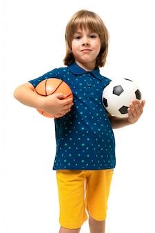 Het beeld van een tiener kaukasische jongen bevindt zich met basketbal en voetbalbal dat op witte achtergrond wordt geïsoleerd