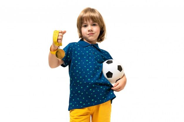 Het beeld van een tiener kaukasische jongen houdt een voetbalbal in één hand en een gouden medaille in andere hand die op witte achtergrond wordt geïsoleerd