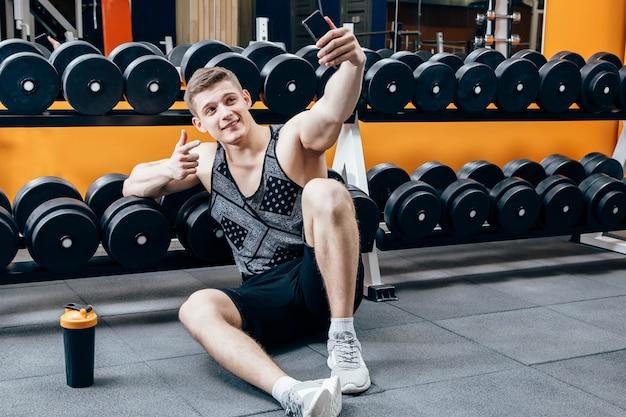 Het beeld van gelukkige jonge sportmanzitting in gymnastiek en maakt selfie.