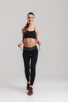Het beeld van gemiddelde lengte van blije vrouw in gymnastiek die en touwtjespringen glimlacht, over grijze muur wordt geïsoleerd