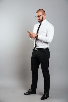 Het beeld van gemiddelde lengte van de jonge ongeschoren mens in glazen en band het babbelen of het werken aan mobiele telefoon, die over grijze muur wordt geïsoleerd