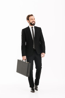 Het beeld van gemiddelde lengte van de knappe mens in zwarte aktentas dragen en pak die opzij kijken, geïsoleerd over witte muur