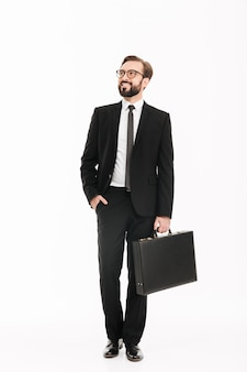 Het beeld van gemiddelde lengte van de rijke zakelijke mens in kostuum en zwarte aktentas dragen en oogglazen die opzij kijken, geïsoleerd over witte muur