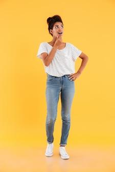 Het beeld van gemiddelde lengte van verraste dame die omhoog exemplaarruimte bekijkt die over geel wordt geïsoleerd