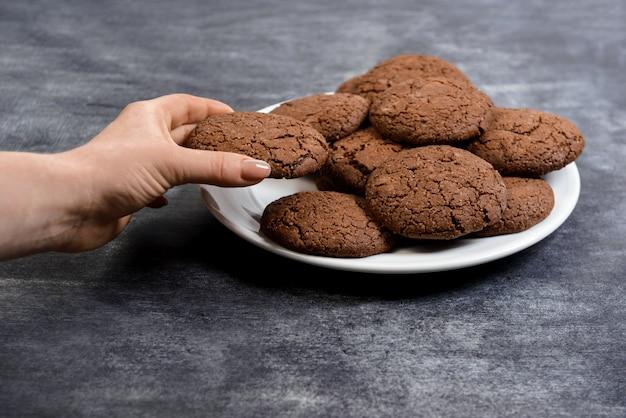 Het beeld van handen houdt chocoladekoekjes op plaat