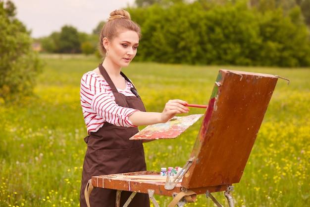 Het beeld van het beeld van de jonge vrouwentekening, die schetsboek gebruiken om in de natuur te tekenen, schildert meisjestribunes met penseel en palet van kleuren, kijkt geconcentreerd, schilderend weidelandschap. concept van kunst.