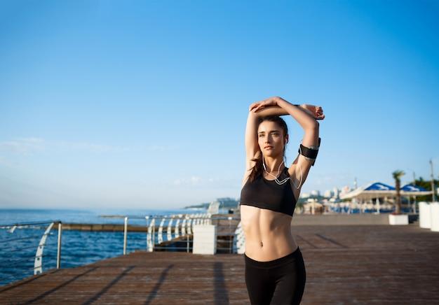 Het beeld van jong mooi fitness meisje maakt sportoefeningen met overzeese kust