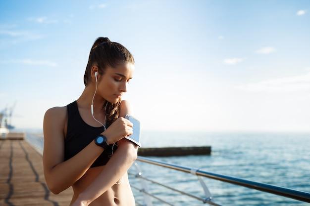 Het beeld van jonge geschiktheidsvrouw luistert aan muziek met overzeese kust op muur