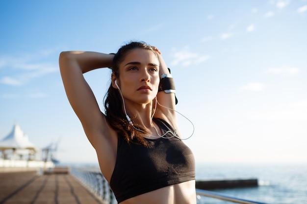 Het beeld van jonge mooie fitness vrouw maakt sportoefeningen met overzeese kust op muur