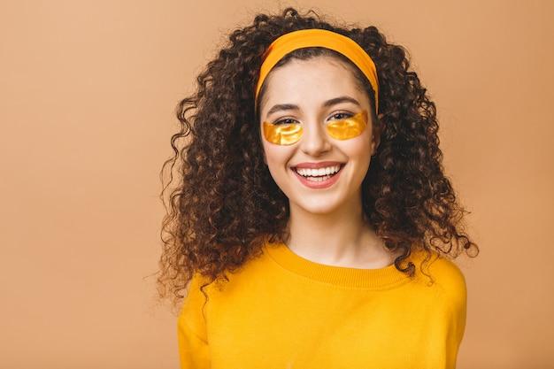 Het beeld van jonge zuivere mooie krullende vrouw die over beige achtergrond wordt geïsoleerd verzorgt haar huid met onder oogvlekken.