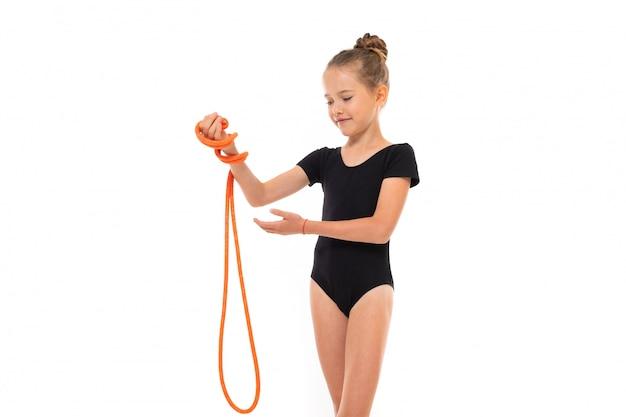 Het beeld van meisjesturner in zwarte trico in volledige hoogte houdt een touwtjespringen in haar hand die op een witte achtergrond wordt geïsoleerd