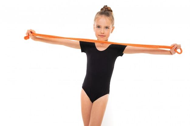 Het beeld van meisjesturner in zwarte trico in volledige hoogte houdt een touwtjespringen in haar handen die op een witte achtergrond worden geïsoleerd