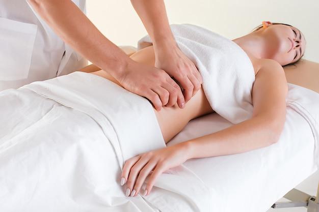 Het beeld van mooie vrouw in massagesalon en mannelijke handen op haar lichaam
