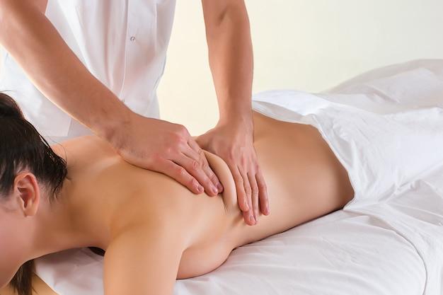 Het beeld van mooie vrouw in massagesalon en mannelijke handen sluit omhoog