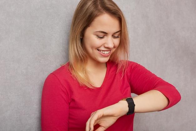 Het beeld van vrolijke blondevrouw bekijkt positief polshorloge, controleert tijd, verheugt zich hebbend vrije tijd alvorens te ontmoeten, gekleed in rode verbindingsdraad, geïsoleerd over grijze muur. mensen en tijdconcept
