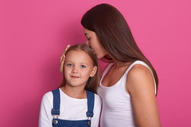 Het beeld van vrouw die witte t-shirt dragen heeft pret met leuk kindmeisje