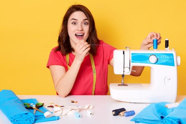 Het beeld van vrouw zet draad op naaimachine