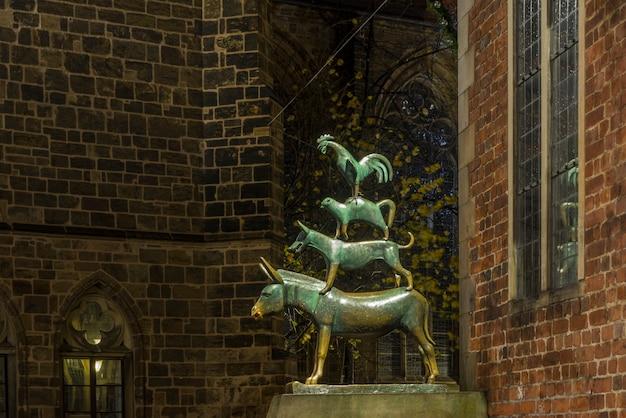 Het beeldhouwwerk van de stadsmusici van bremen 's nachts. centraal plein van bremen