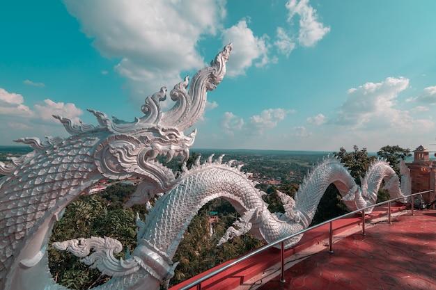 Het beeldhouwwerk van witte naga prayanak met blauwe hemel en wolkenachtergrond.