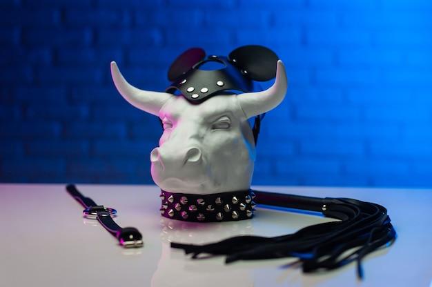 Het beeldje van een witmetalen stier in een leren masker en accessoires voor bdsm-spellen
