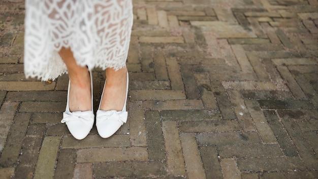 Het been van de bruid met kledingsschoenen op bestrating