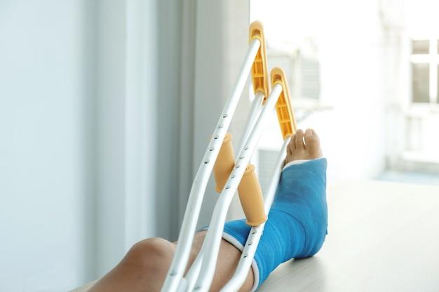 Het been van de man gebruikt krukken om te lopen na een operatie herstel letsel gebroken botten.