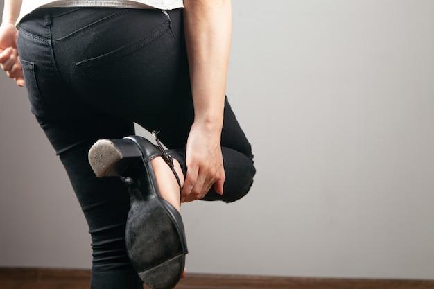 Het been van de vrouw doet pijn op een grijze achtergrond Premium Foto
