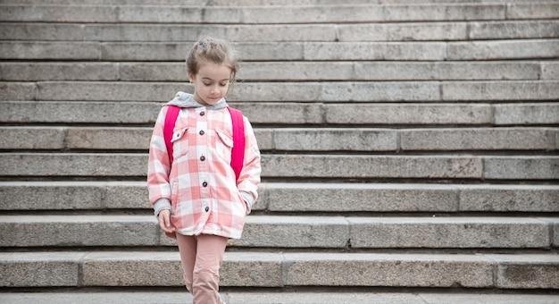 Het begin van de lessen en de eerste dag van de herfst. een lief meisje dat voor staris staat