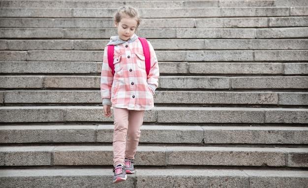 Het begin van de lessen en de eerste dag van de herfst. een lief meisje staat tegen de achtergrond van een grote brede trap.