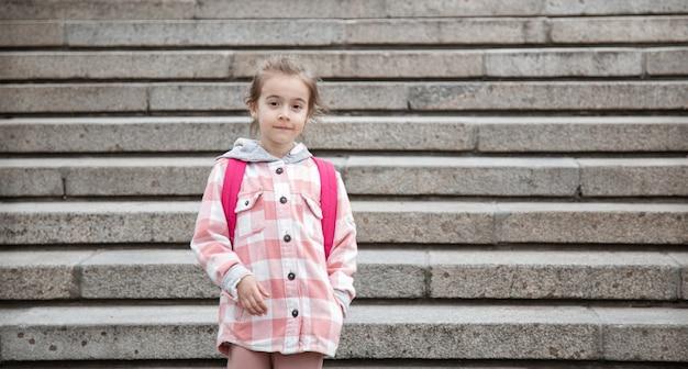 Het begin van de lessen en de eerste dag van de herfst. een lief meisje staat tegen een grote brede trap.