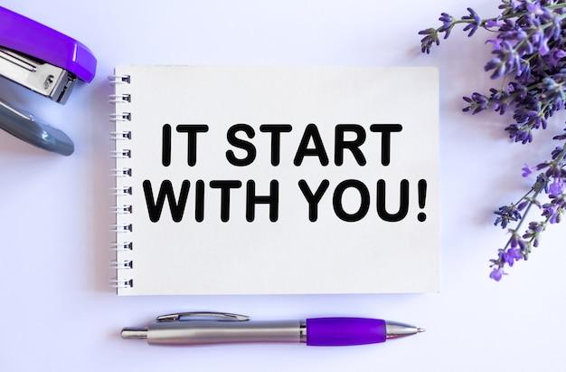 Het begint met jou. bovenaanzicht van open blanco notitieblok met lavendelboeket op witte achtergrond