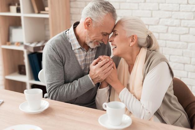 Het bejaarde paar houdt handen samen. liefde tot aan de dood.