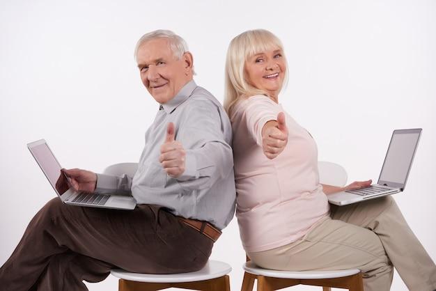 Het bejaarde paar met laptop toont duimen
