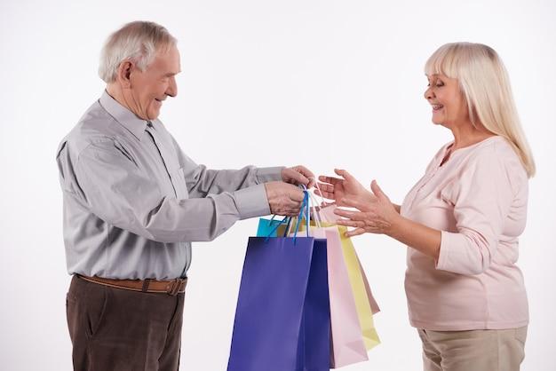 Het bejaarde paar met pakketten gaat winkelend in wandelgalerij.