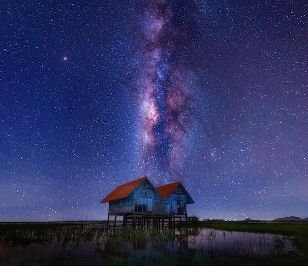 Het bekende tweelinghuis in talaynoi, pattarung. met melkweg in het midden van de nachtelijke hemel en weerspiegeling van het huis op water achtergrond.