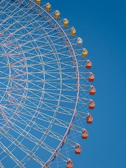 Het bekijken van reuzen reuzenrad tegen de blauwe hemel