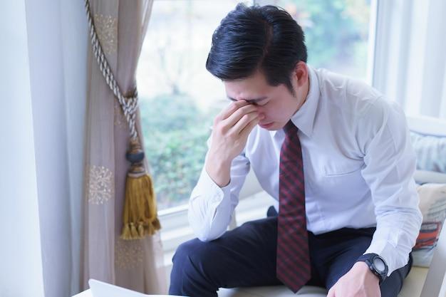 Het beklemtoonde aziatische jonge hoofd van de zakenmanholding met handen die neer kijken. negatieve menselijke emotie gezichtsuitdrukking gevoelens.