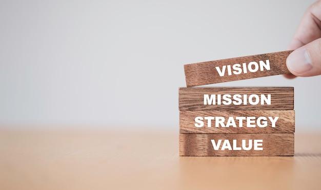 Het belangrijkste succesconcept van het bedrijf, met de hand houten kubussenblokken plaatsen die de missiestrategie van de schermvisie en waardebepaling afdrukken.