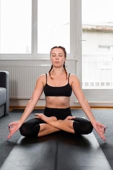 Het beoefenen van yoga lotuspositie thuis concept