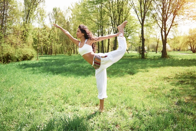 Het beoefenen van yoga van een mooi meisje in de ochtend op kruiden onder de woorden van de zon.