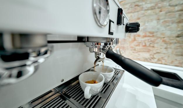 Het bereiden van twee kopjes koffie op een espressomachine in een coffeeshop.
