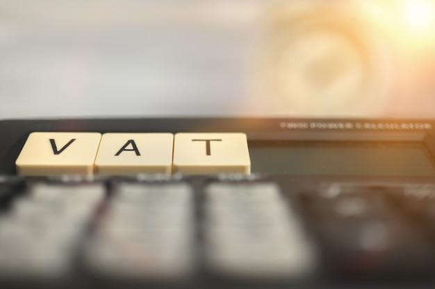 Het berekenen van de btw-heffingen. btw-woord op houten blok en rekenmachine op de zakelijke desktop