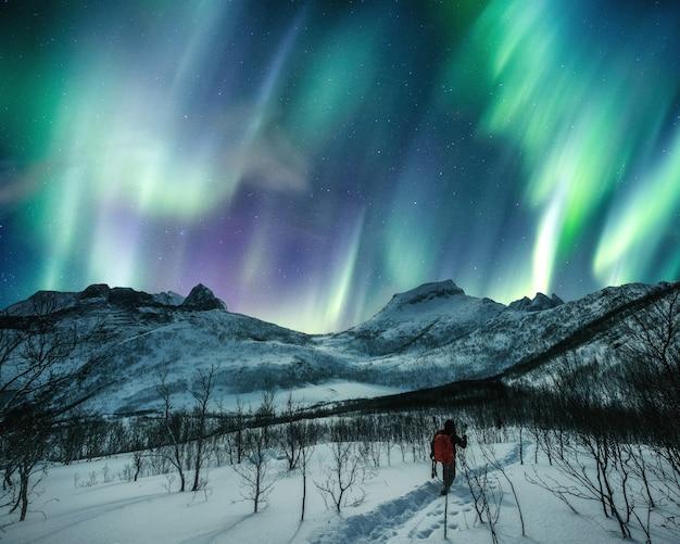 Het bergbeklimmen van de mensenreiziger op sneeuwheuvel met aurora borealis in de nachthemel bij senja-eiland