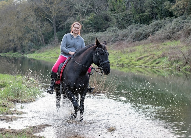 Het berijdende meisje leidt haar zwarte paard op