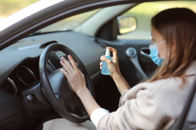 Het bespuiten van antibacteriële ontsmettingsnevel dient auto in, concept van infectiecontrole. ontsmettingsmiddel om coronavirus, covid-19 te voorkomen. spuitfles. vrouw die in medisch beschermend masker draagt dat een auto drijft.