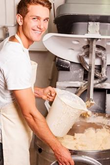 Het beste deeg voor ons gebak. zelfverzekerde jongeman in schort die op de deegmengmachine drukt en glimlacht