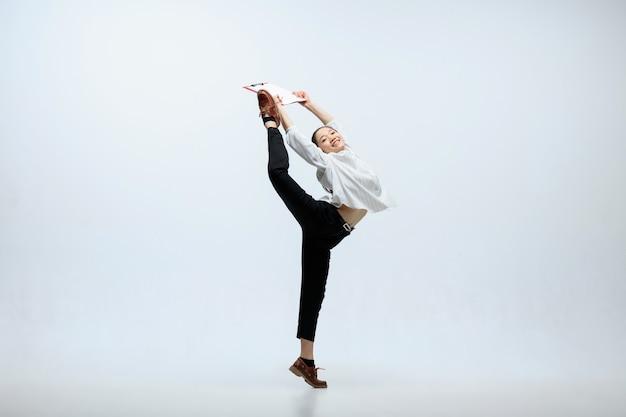 Het beste resultaat kan inspirerend zijn. gelukkige vrouw die op kantoor werkt, springt en danst in vrijetijdskleding of kostuum dat op witte studioachtergrond wordt geïsoleerd. bedrijf, start-up, werkend open-ruimteconcept.