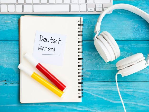 Het bestuderen van nieuwe taalhulpmiddelen op blauwe houten achtergrond